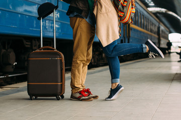 Closeup shot of woman feet standing on tiptoe while embracing her man at railway platform for a farewell before train departure. A travelling luggage is on the foreground. Travel and tourism concept