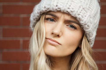 Portrait of a beautiful blonde woman wearing a large warm winter hat. Nice background of this composition is created of red brick wall.