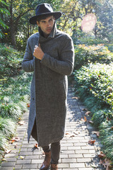 Handsome mature male model with beard, wearing black hat and long gray coat, he is walking in autumn garden and searching for the ray of sun.