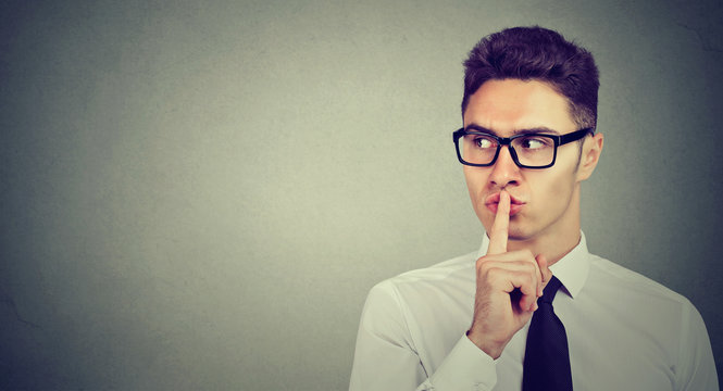 Secret guy. Man saying hush be quiet with finger on lips gesture looking to the side
