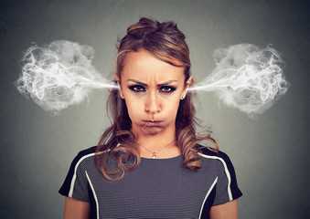 Closeup portrait of angry young woman, blowing steam coming out of ears