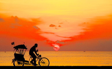 silhouette old man ride Tricycle on colorful sky background