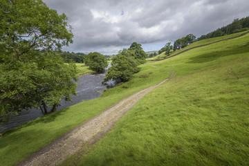 Characteristic English Landscape green field and the river Wharfe with path leading into the countryside