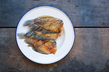Crispy gourami fish in white plate on wood background