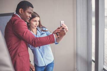Young business team outdoors in urban setting taking a selfie