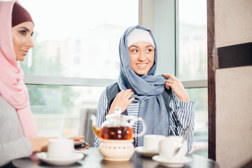 Pretty young Muslim woman with a cup of coffee or tea in action