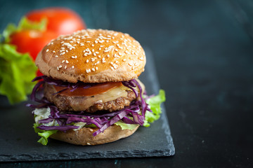 Burger with purple cabbage over black textured board