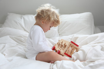baby girl in parent's bed with wooden toy, bedtime and sleep routine