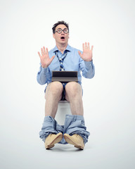 Funny man in tie with tablet pc sitting on the toilet.