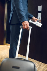 businessman with suitcase calling elevator