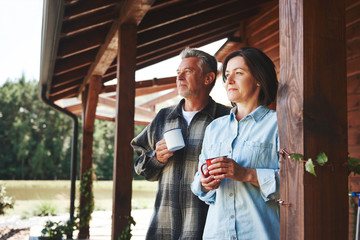 Mature couple standing on cabin veranda, holding tin cups, looking at view