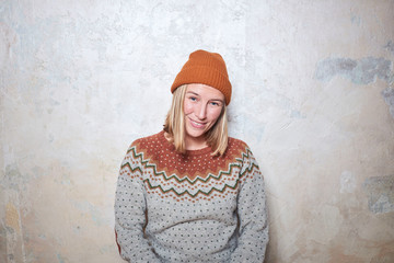 Portrait of woman wearing jumper and knitted hat, smiling