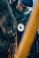 Blacksmith grinding metal on machine in metal workshop
