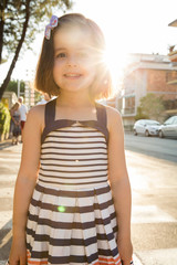 Portrait of girl in street looking at camera smiling