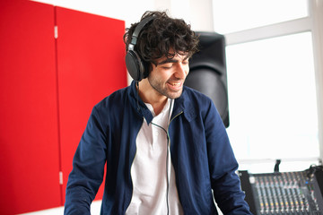 Young male college DJ student listening to music on headphones