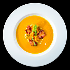 Delicious and appetizing pumpkin cream soup with chips in a white plate isolated on black background. Autumn menu in an Italian restaurant. Photo for menu design, top view, flat, overhead