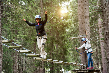 Friends in forest using high rope course