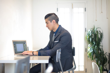 Young businessman typing on laptop at desk