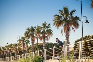 Man leaning against railings looking away, Cagliari, Sardinia, Italy, Europe