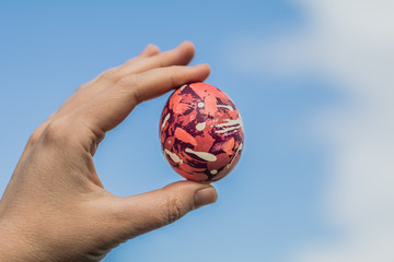 Hand holding modern unusual Happy easter handmade colorful egg outside sky background