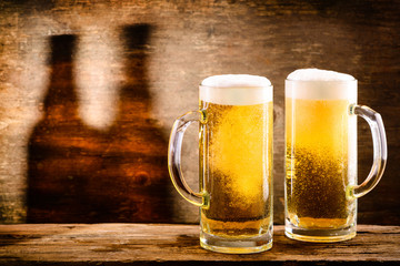 Two fresh cold light beer in a beer mug with foam and drops of water on brown background