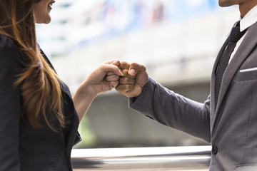 Business people of a Partnership Team Giving Fist Bump after complete deal. Successful Teamwork Partnership in an Office with bokeh background