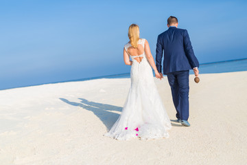 Bride and groom walking away on the beach, romantic background concept