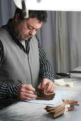 Shoemaker looking at samples in his workshop