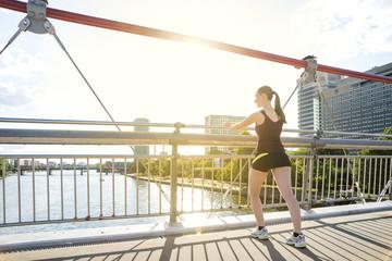 Germany, Frankfurt, young woman stretching on bridge
