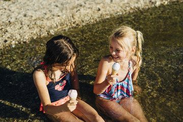 Two girls sitting in water at lakeshore eating icecream