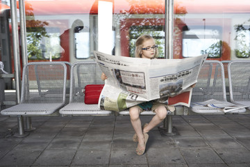 Portrait of little girl sitting at platform reading newspaper