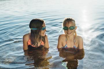Two smiling friends with swimming goggles at lakeshore