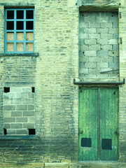 neglected and abandoned industrial warehouse and factory building with bricked up windows and green door in halifax yorkshire in britain