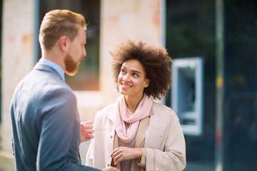 Two business people in an informal conversation in front of a business building