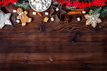 Christmas gingerbread, spruce branches on dark wooden background