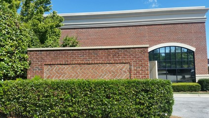 Brick walls and shrubbery in sunny outdoor retail shopping center