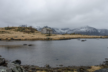 Wooden hut in front of a small lake in the Lofoten Islands in Norway in the background snowy mountains