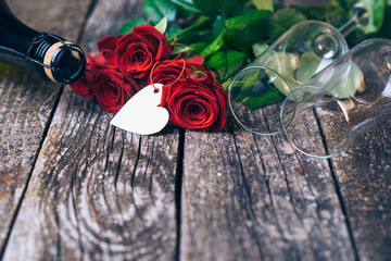 Bouquet of red roses, two glasses, bottle of wine, gift box with tag on vintage wooden board. Valentines day.