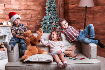 Beautiful happy laughing children playing on the sofa in a Christmas interior with Christmas tree and fireplace. The concept of a family holiday