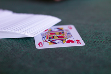 queen of hearts card on a green mat
