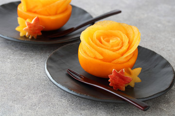 Persimmon rose in hollowed-out persimmon with maple leaves on black plate 柿のデザート