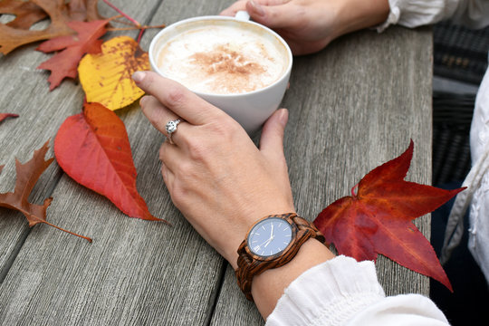 Woman with elegant hands wearing a wooden watch holding a cup of coffee against a rustic table with colorful autumn leaves
