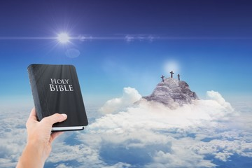 Composite image of hand holding bible