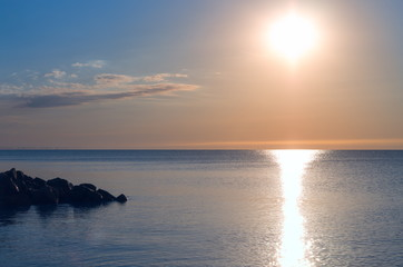 Fotomurais - stone ledge on the seashore. Sunrise. sea horizon, reflection. sun, sky with clouds