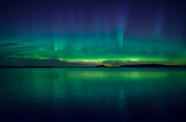 Northern lights dancing over calm lake in Farnebofjarden national park in Sweden.