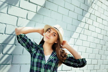 Happy young woman in hat and plaid shirt smiling, near blue brick wall with copy space