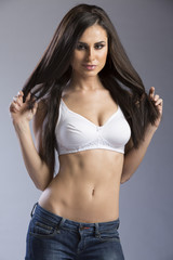 Full body portrait of young pretty woman wearing white lingerie top with jeans
