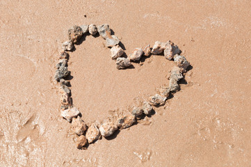 Heart lined with stones on the sandy beach of the sea