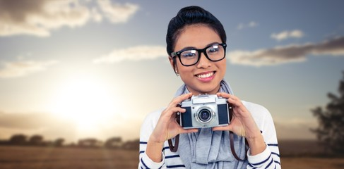 Composite image of smiling asian woman holding camera