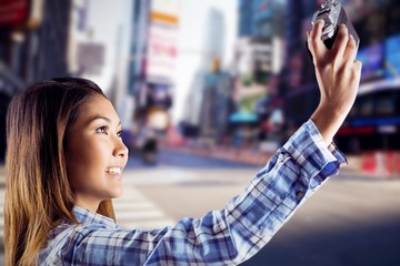Composite image of smiling asian woman taking picture with
